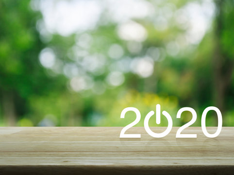 2020 start up business flat icon on wooden table over blur green tree in park, Happy new year 2020 concept