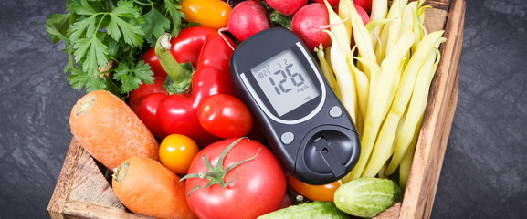 Glucometer with fresh vegetables as source minerals and vitamins. Diabetes, healthy lifestyles and dieting