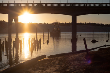 Evening light on the Siuslaw River and bridge, with a fishing boat on the water in Florence, Oregon.