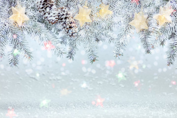 christmas tree branch under snow decorated with glowing star lights garland. frosty winter background
