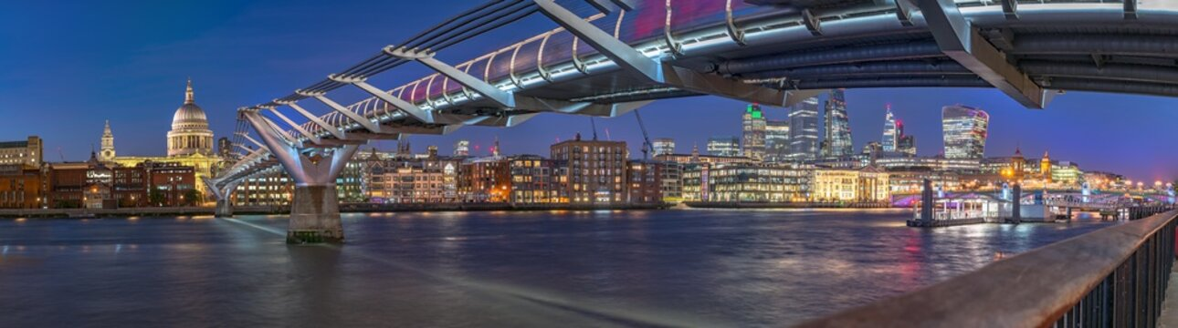 Night panorama of the Thames river with Millennium bridge and Saint Paul's Cathedral and the City skyline in the background. Panoramic view cityscape of London, United Kingdom