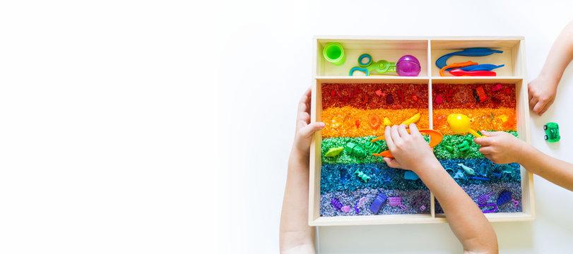 Sensory box with rainbow rice inside. Montessori material baby Copy Space