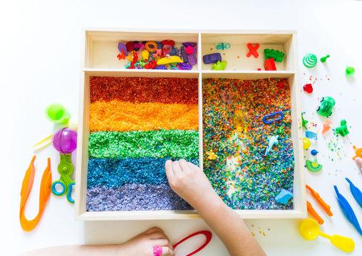 Sensory box with rainbow rice inside. Montessori material baby