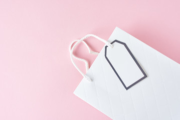White shopping bag on pink background, top view
