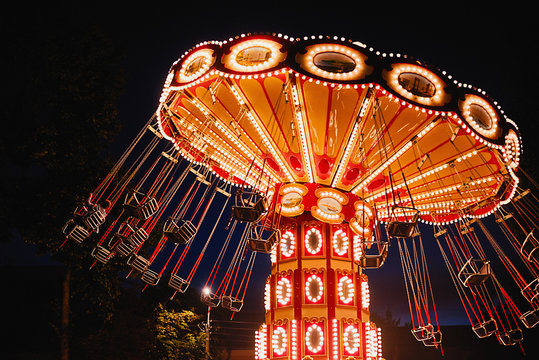 Illuminated swing chain carousel in amusement park at the night