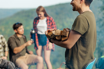 cheerful tourist during hiking, holding wood for a campfire. preparing to make a fire. close up side view photo, romantic couple is talking in the background of the photo, blurred background