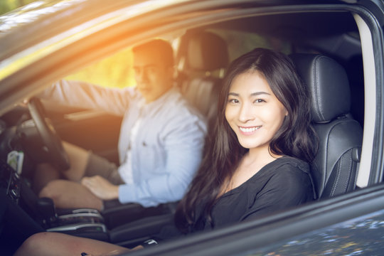 woman and man Enjoying to travel. Asian couple sitting on the front passenger seats ,they smiling while  driving a car  on the road
