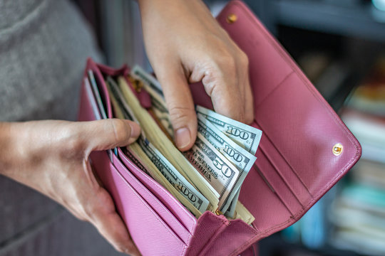 Woman taking out US dollar bills from her pocket wallet (depth of field photography).