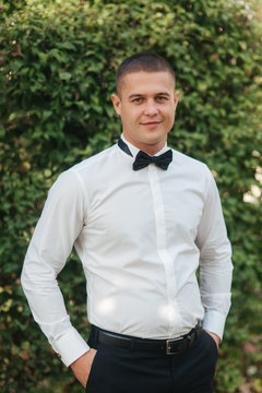 Young man in white shirt with black tie bow stand outside