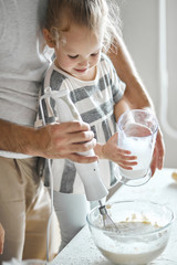 man is working with blender while his kid holding a jar of water. close up cropped photo