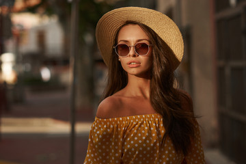Closeup outdoor portrait of young beautiful caucasian young woman with long brunette hair wearing yellow polka dot dress, sunglasses and thatch hat. Summer sunny evening street Wall mural