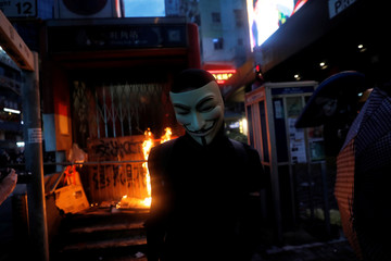 A masked anti-government protester leaves after helping to set a fire at the entrance of a metro station, in Hong Kong