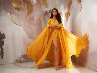 Young beautful caucasian woman with long wavy brunette hair in yellow flying dress posing against wall. Vogue style fashion portrait Wall mural