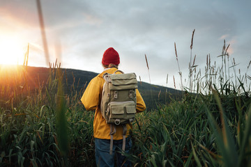 Back view of man tourist with backpack standing in front of the mountain massif while journey by scandinavian. Male traveler wearing yellow jacket explore national park and hiking outdoor landscape