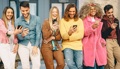 Group of trendy friends using mobile smartphones outdoor - Millennial young people having fun with new technology apps for social media - Concept of youth culture generation z and technology