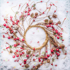 Christmas wreath with red berries on snow, top view. Frame. Copy space