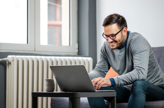 Handsome man with glasses enjoying working on laptop from home