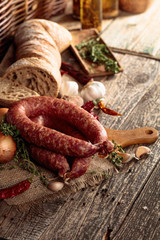 Wall Mural - Dry-cured sausage with bread and spices on a old wooden table.