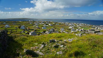 Auf Irland mit einer Aufsicht auf eine kleine Siedlung und Meer
