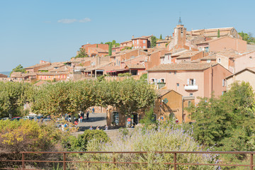View of hilltop medieval ochre village of Roussillon, one of the most beautiful villages of France in a sunny summer day.