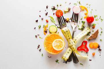 vegetables on forks with measuring tape on a white background with place for text. concept diet, weight loss, fat loss