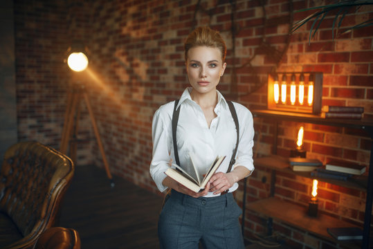 Business woman in strict clothes poses with book