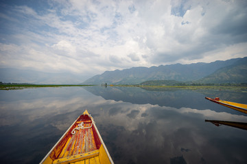 View over traditional boat or shikara - a type of wooden boat at Dal Lake, Khasmir. Shikara are of varied sizes and are used for multiple purposes, including transportation of people.