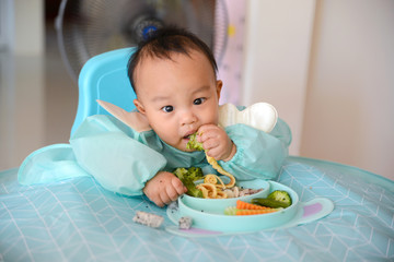 Asian baby boy 7 months old eating with Baby Led Weaning (BLW) method, Self-Feeding