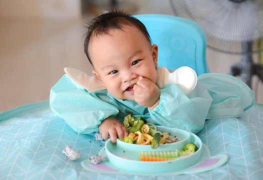 Happy eating Asian baby boy, 7 months old eating with Baby Led Weaning (BLW) method, Self-Feeding