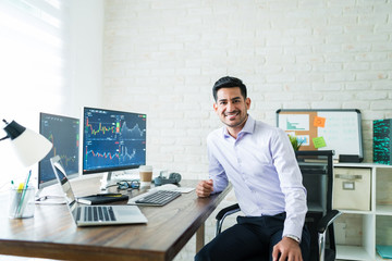 Confident Handsome Young Stock Broker Working At Home
