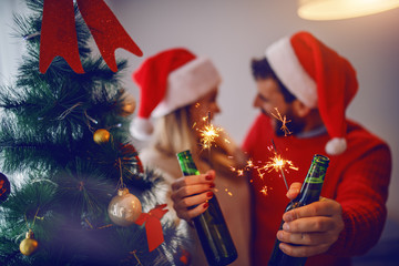 Happy caucasian couple in sweaters and with santa hats on heads celebrating new year and holding...