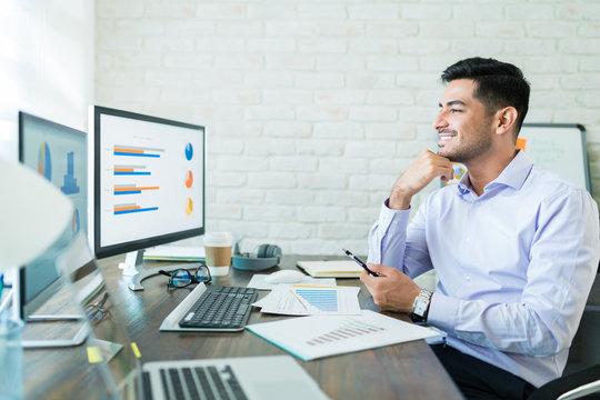 Freelance Sales Professional Examining Data At Desk