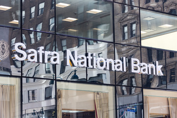 NEW YORK, USA - MAY 15, 2019: The glass windows of the Safra National Bank building reflect the facades of other buildings on Fifth Avenue, Midtown Manhattan.