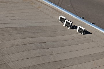 Heat wave concept image consisting of 3 air conditioners on a roof of a building.
