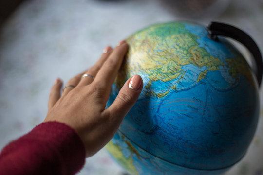 Globe og the World Map Travel Explore Destination Concept. Hand spinning the globe