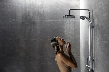 Woman taking shower in dark modern bathroom interior