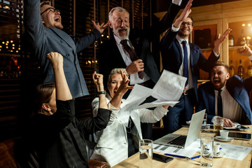 Large business team enthusiastically exulting in bright office, mirthfully raising hands smiling broadly and throwing paper documents up at meeting