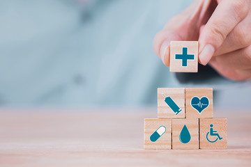 Businessman chooses a emoticon icons healthcare medical symbol on wooden block , Healthcare and medical Insurance concept