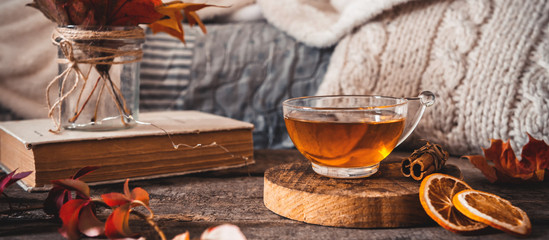 Foto auf Leinwand Tee Cozy autumn or winter at home. A cup of tea, autumn casts a book a garland on a wooden table near a bed with warm plaids. Lifestyle autumn hygge lagom?concept of a holiday and autumn weekend.Banner