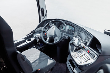 The driver cab of a bus with a steering wheel and various devices and gadgets
