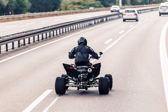 All-terrain vehicle quadbike riding on a highway