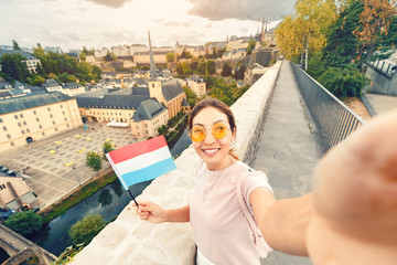 Asian tourist girl takes a selfie with the flag of Luxembourg against the background of the old quarter of the city of Grund and the Church. Wall mural