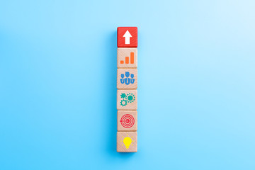 Business development strategy and Action plan concept, wooden blocks with business process management icons and arrow up on blue background, copy space