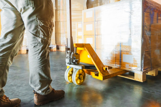 warehouse worker working with hand pallet truck unloading shipments goods pallet at warehouse storage.