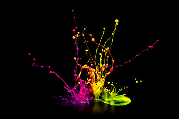 Colorful paint splashing on audio speaker isolated on black background