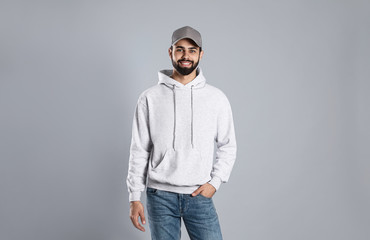 Wall Mural - Portrait of young man in sweater on grey background. Mock up for design