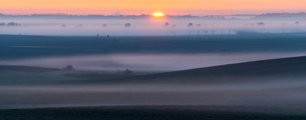 Foto op Canvas Nachtblauw sunrise over fields reminiscent of the Italian Tuscan landscape on a beautiful foggy morning