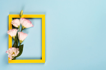 Empty yellow frame with flowers eustoma on blue paper background with copy space. Flat lay. Love concept