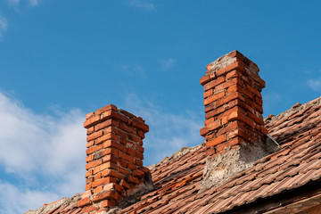 Two traditional red brick chimneys on an old clay tile roof against a blue sky. Chimney in need of sweeping and repair. Preparing for winter concept.