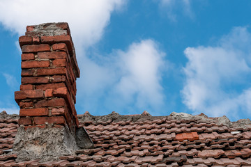 Old red terracotta tile roof with a damaged traditional large brick chimney in need of repair, on a blue sky background. Home winter preparations.
